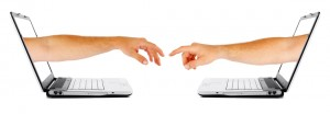 Two human hands coming out two seperate computers, reaching out for each other. Isolated on a white background